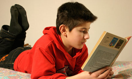 A young boy lying on his bed, reading a book